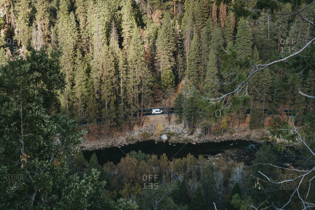 Camper van drives along the river bend