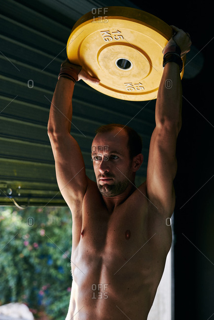 Shirtless fit young man working out with steel disc at indoors garage
