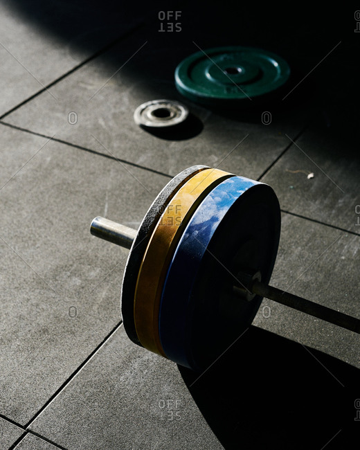 Blue, yellow and black heavy discs at indoors gym in rubber floor