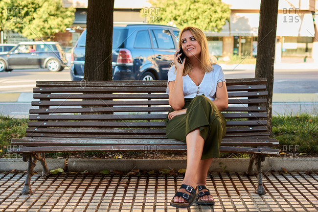Young woman calls with her phone while sitting on an outdoor bench