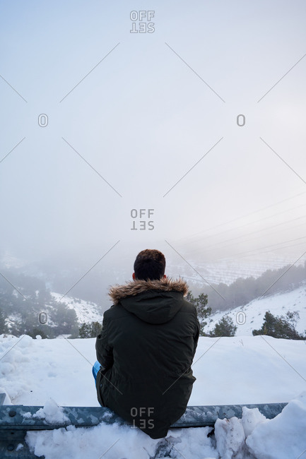 Young man is looking at the horizon on a snowy day