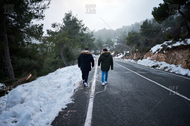 Two friends are walking down a road surrounded by snow
