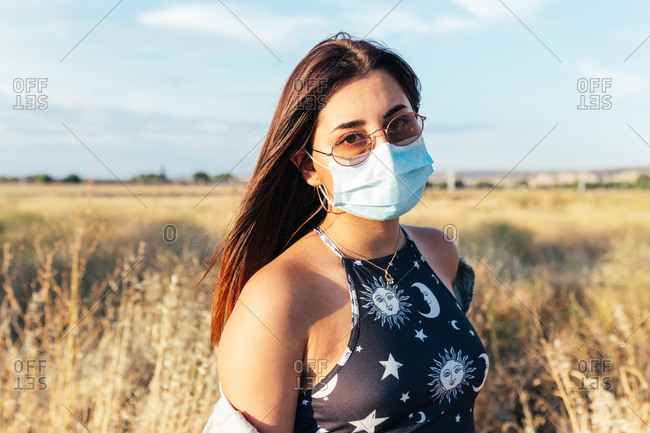 Serious teenager with a medical mask and sunglasses in the countryside