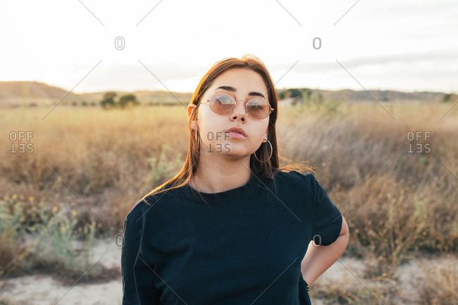 Teenager in sportswear and sunglasses at sunset in the countryside