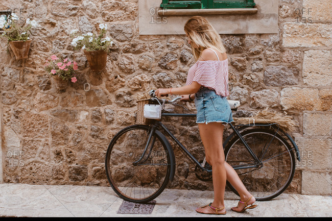 Blonde woman choosing the bike like transport in majorca