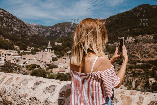 Woman on a trip taking a photo with phone of the landscape in majorca