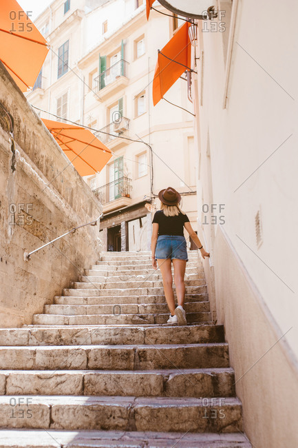 Back view of adventurous traveler woman walking upstairs in majorca