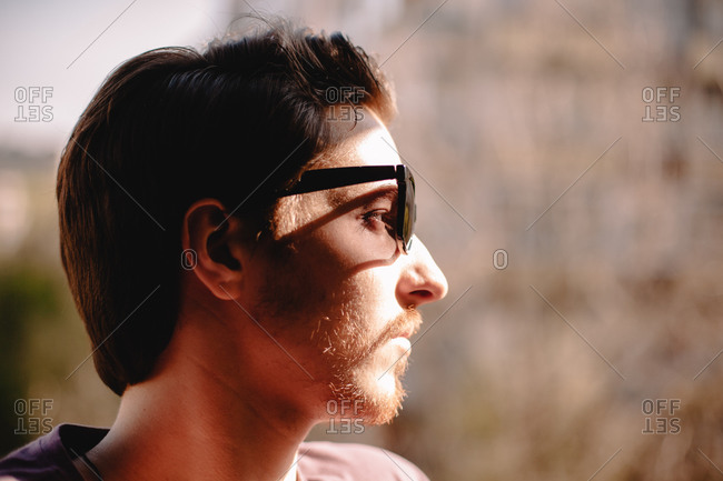 Close up portrait of young depressed man wearing sunglasses