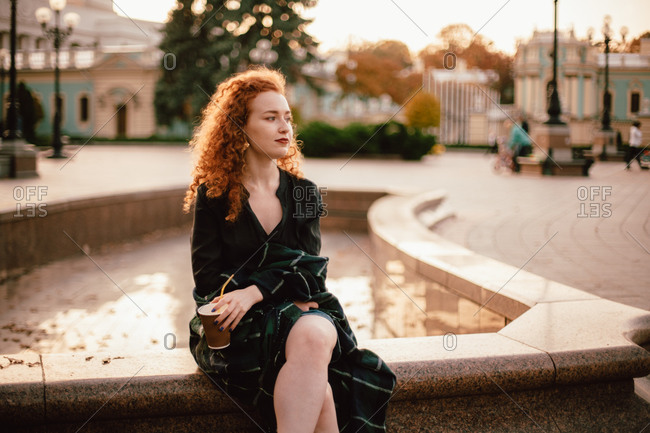 Young thoughtful red head woman sitting on fountain in city