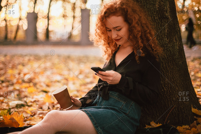 Happy young woman using smart phone sitting by tree in park in autumn