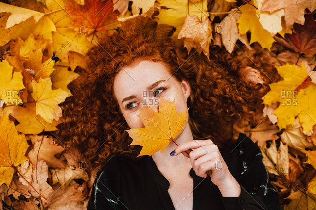 Young woman holding leaf on face lying in orange leaves in autumn park
