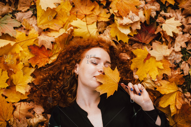Young woman holding leaf lying in orange leaves in autumn park