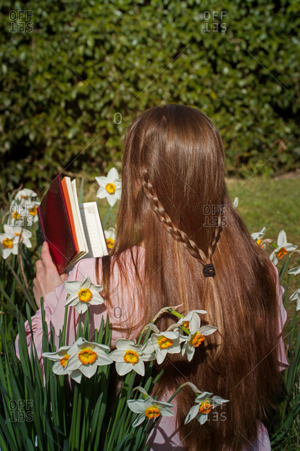 Backview of brown-haired girl reading a book sitting among flowers