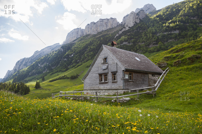 Alpine hut below limestone spires in alpstein, appenzell, switzerland
