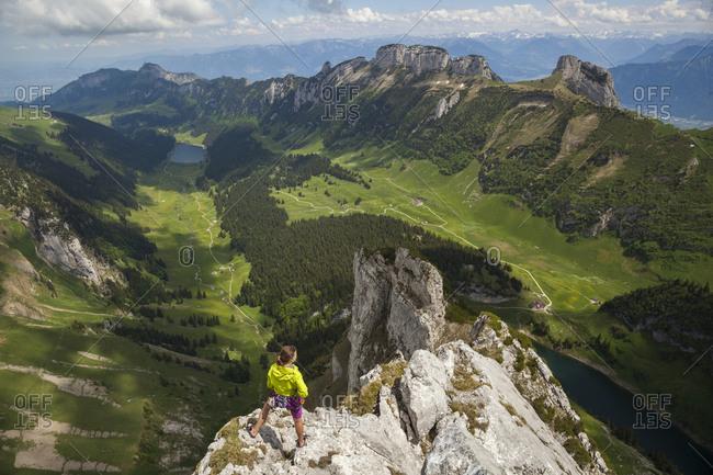 Rock climber on summit over valley, alpstein, appenzell, switzerland