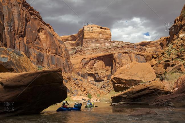 People paddle packrafts below high cliffs on escalante river, utah