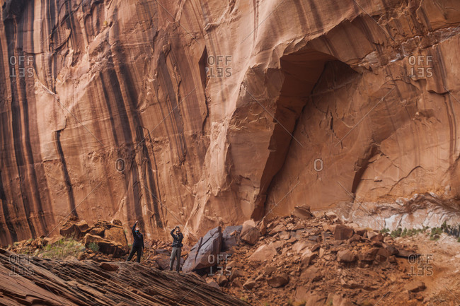 People below high sandstone canyon walls near escalante river, utah