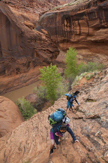 Packrafters hike coyote gulch, utah after descending escalante river