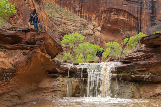 People hike across waterfall in sandstone canyon, coyote gulch, utah