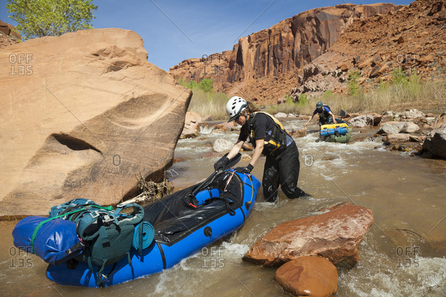 People walk packrafts through shallow part of escalante river, utah