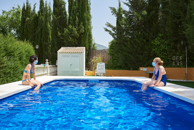 Two women in a pool. they wear protection masks against the corona virus