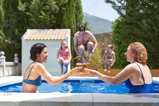 Women in a pool. they toast celebrating that they are on vacation.