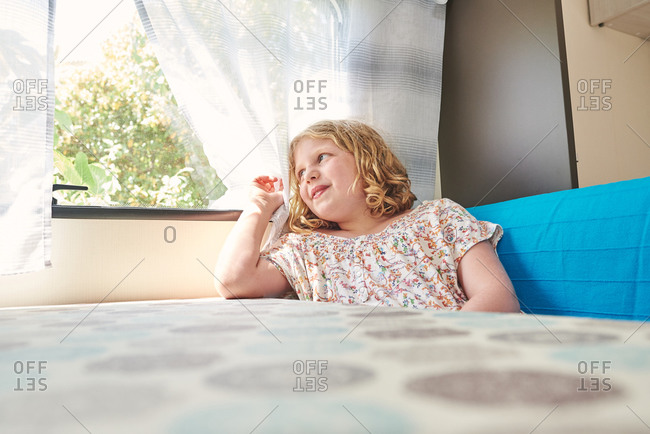 Young girl in a caravan. she is holy looking out the window.