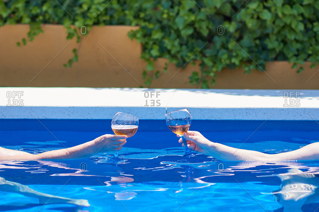 Two people toast in a pool. closed shot of toasting hands.