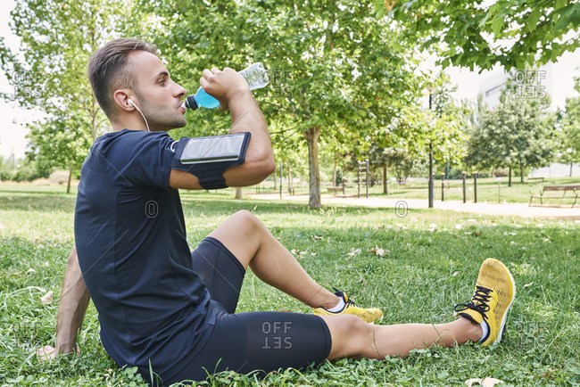 Man drinking sports drink after training. he is in an outdoor park.