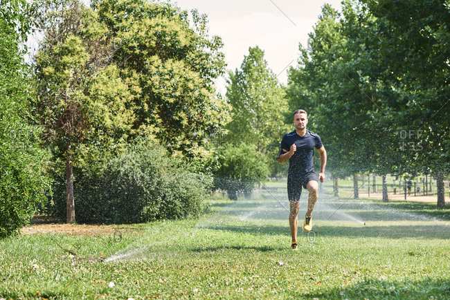 Young man training in a park, he is jogging.