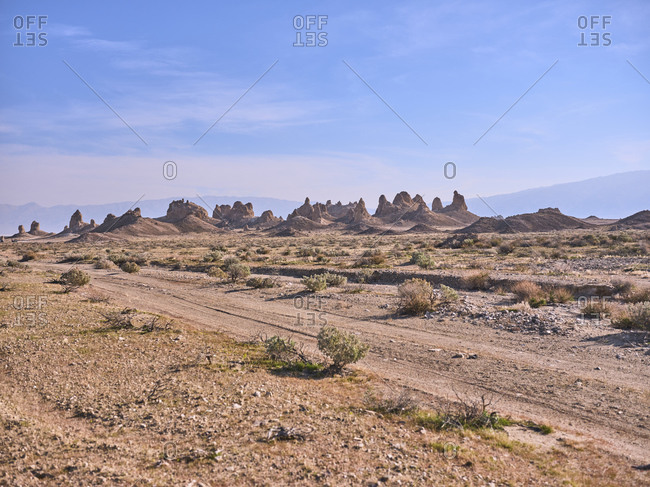 A dusty dirt road winds through the desert to the trona pinnacles.