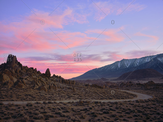 Cotton candy clouds, a dirt road winds through rock formations.