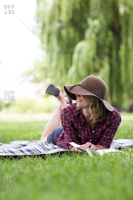 A young woman reads a book in a park in the columbia gorge.