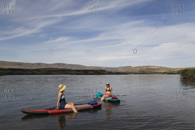 Two female friends sit on their sups on the columbia river in oregon.