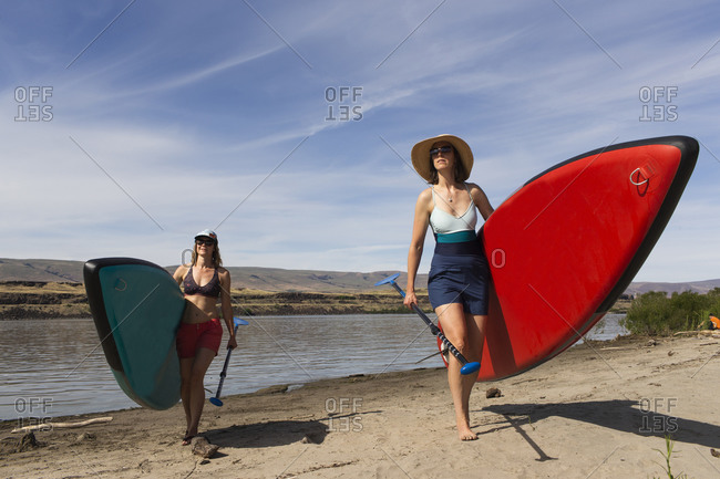 Two women carry their sups from the columbia river in oregon.