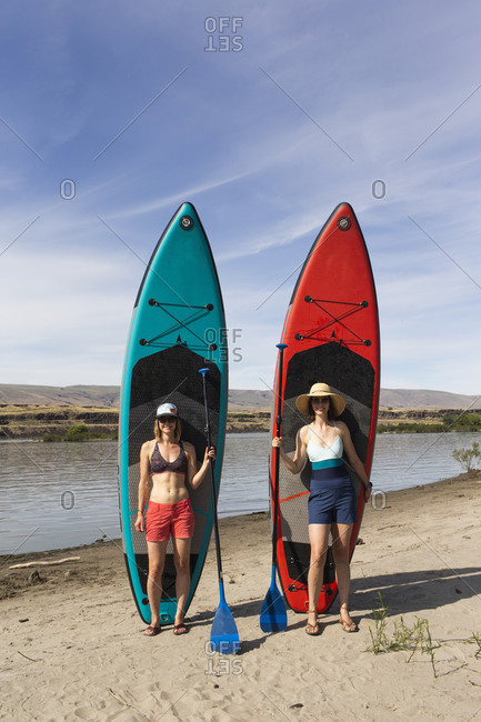 Two women stand in front of their sups near the columbia river in or.