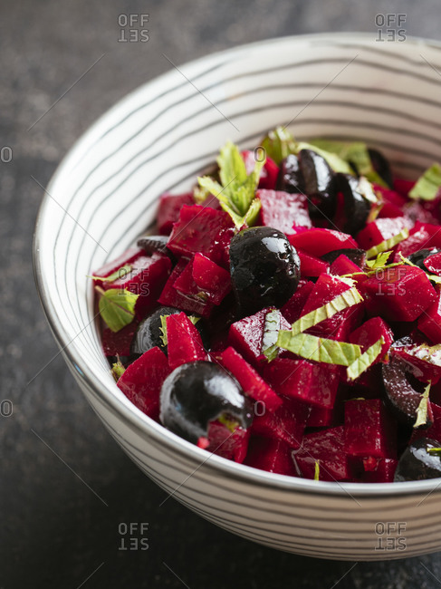 Bowl with a beet salad with minted beets, olives and fresh mint leaves