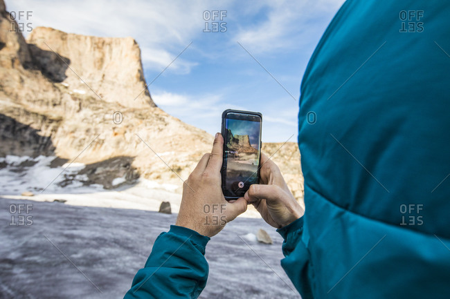 Climber takes photo of asgard mountain with his phone.