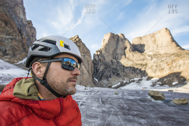 Portrait of climber wearing helmet and sunglasses below mountain summi