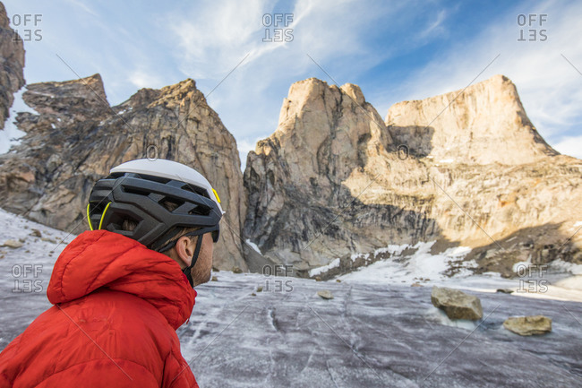 Climber wearing helmet looks up at mount asgard