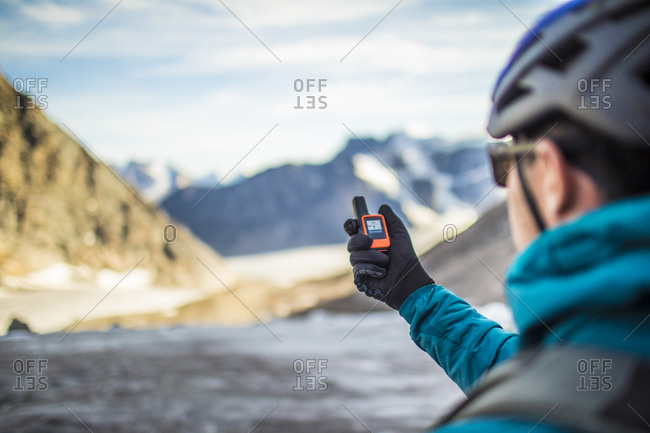 Climber uses a gps to navigate in a high mountain pass.