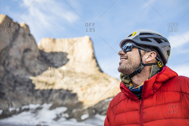 Smiling side view portrait of mountain climber below summit.