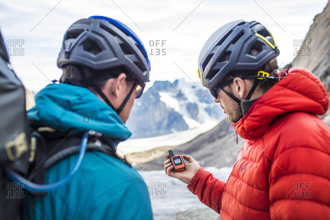 Two climbers use a gps to navigate mountain terrain.