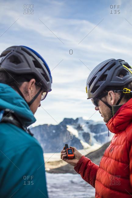 Two explorers use a gps to navigate mountain terrain.