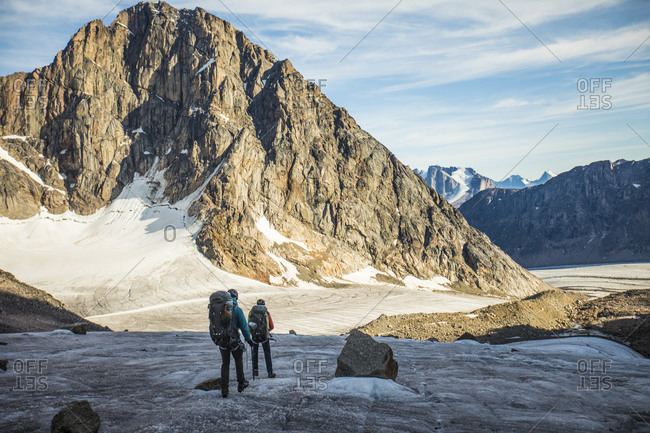 Two backpackers cross a glacier below mountain range.