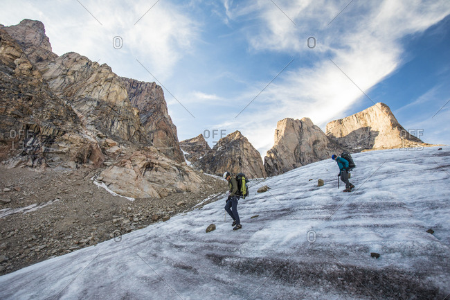 Two mountain climbers traverse a glacier below mount asgard.