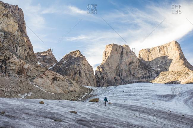 Mountain climber traverses a glacier below mount asgard.