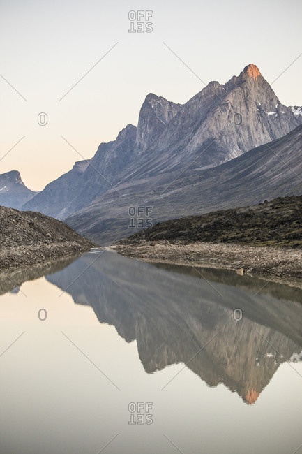 Alpenglow on mt. odin reflecting in summit lake, baffin island.