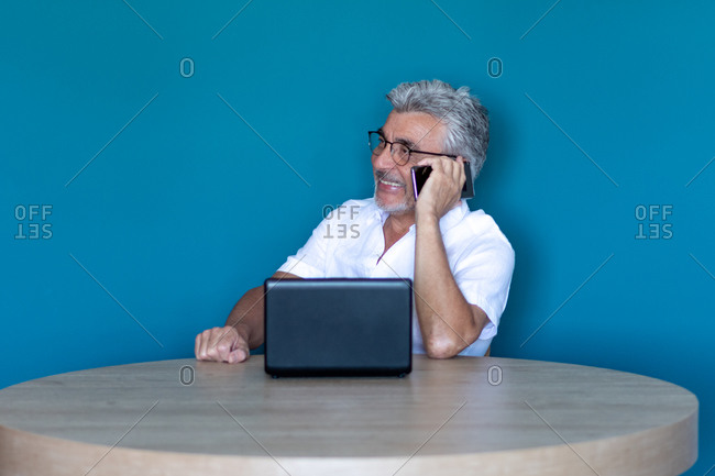 Older man with grey hair and glasses teleworking from home with his laptop, smiling and talking on his mobile phone.