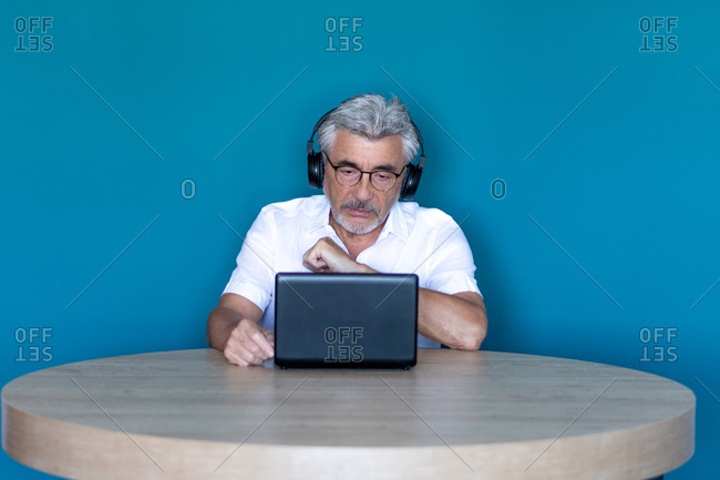 Older man with gray hair and glasses studying from home with his laptop and black headphones.